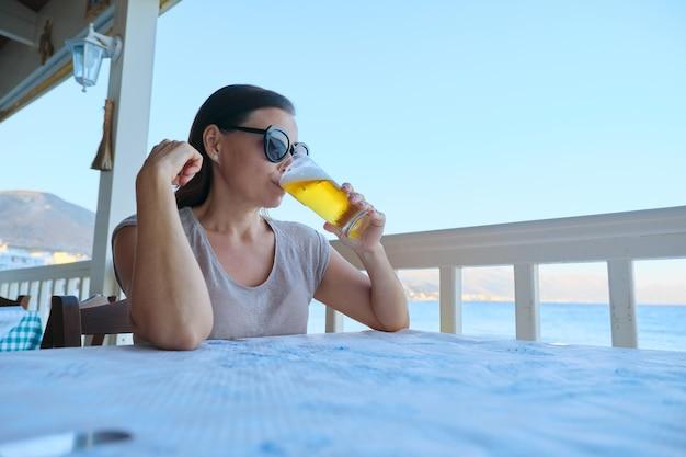 Dojrzała piękna kobieta, odpoczynek, siedząc w kawiarni morskiej, picie zimnej szklanki piwa