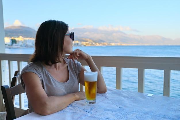 Dojrzała piękna kobieta, odpoczynek, siedząc w kawiarni morskiej z zimną szklanką piwa