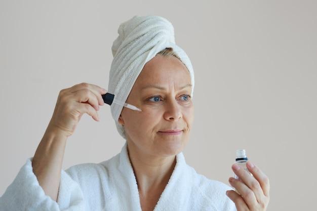Dojrzała piękna kobieta w szlafroku z białym ręcznikiem na głowie używa serum przeciwzmarszczkowego