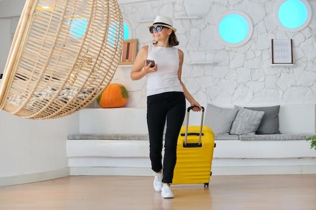 Dojrzała piękna kobieta z walizką w holu nowoczesnego hotelu uzdrowiskowego