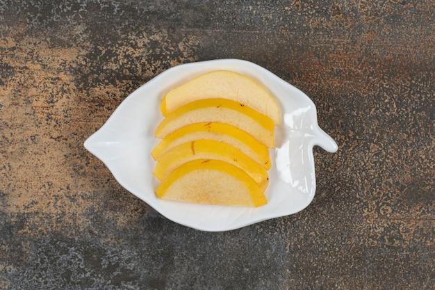 Dojrzała pigwa w plasterkach na talerzu w kształcie liścia
