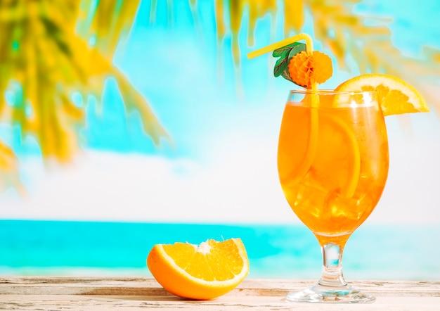 Dojrzała pomarańcza w plasterkach i szklanka soczystego napoju cytrusowego