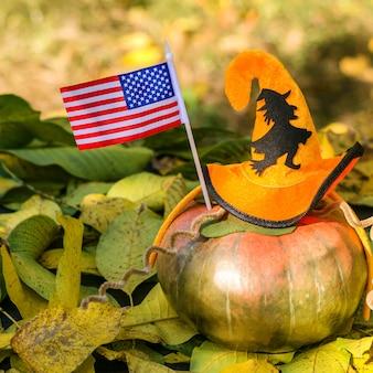 Dojrzała pomarańczowa dynia ozdobiona kapeluszem halloween, leży na żółtych jesiennych liściach.
