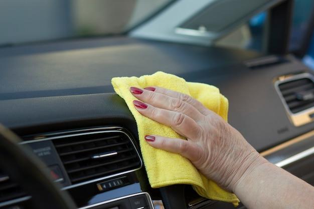 Dojrzała pracownica czyszczenia deski rozdzielczej samochodu żółtą ściereczką z mikrofibry.