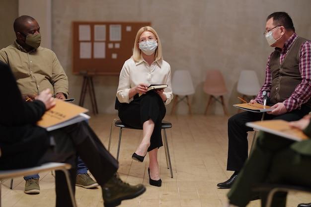 Dojrzała psycholog w eleganckim kamuflażu i masce ochronnej siedząca na krześle między międzykulturowymi pacjentami płci męskiej podczas sesji
