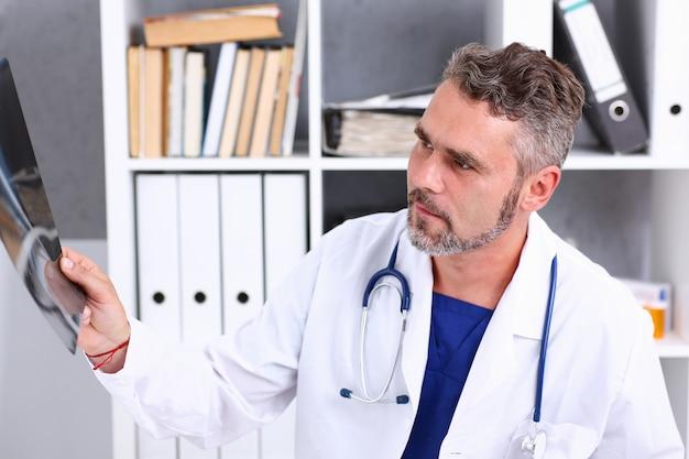 Dojrzała samiec lekarka trzyma rękę i patrzeje fotografię xray