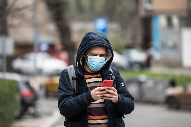 Dojrzała samiec z telefonem w rękach stoi outdoors w chronić medyczną maskę
