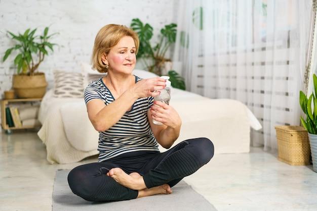 Dojrzała śliczna zmęczona kobieta po treningu sportowego pije wodę z butelki w domu