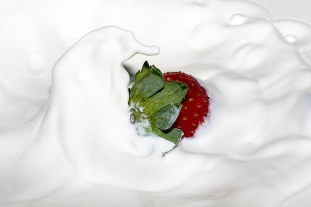 Dojrzała słodka świeża truskawka w śmietanie z plamami i bąbelkami z bliska