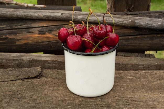 Dojrzała słodka wiśnia w białej filiżance na drewnianym ogrodzeniu.