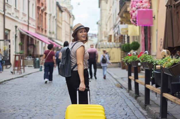 Dojrzała uśmiechnięta kobieta podróżuje w turystycznym mieście z walizką