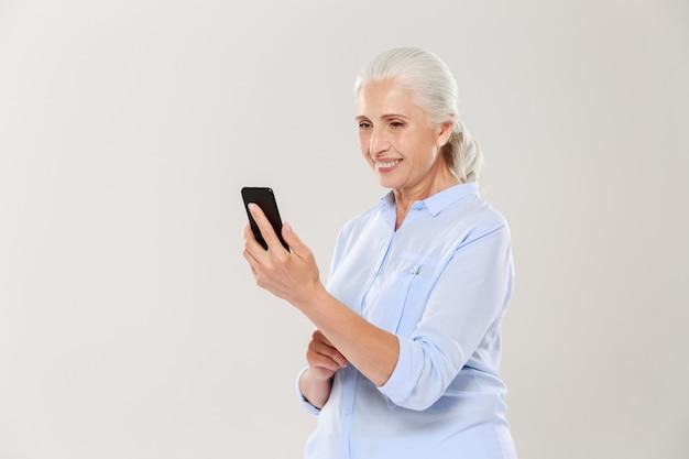 Dojrzała uśmiechnięta kobieta używa smartphone odizolowywającego