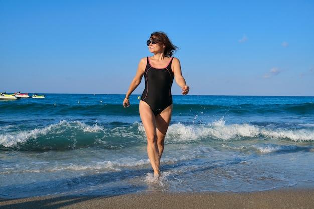 Dojrzała uśmiechnięta kobieta w stroju kąpielowym z okularami przeciwsłonecznymi spaceru wzdłuż plaży