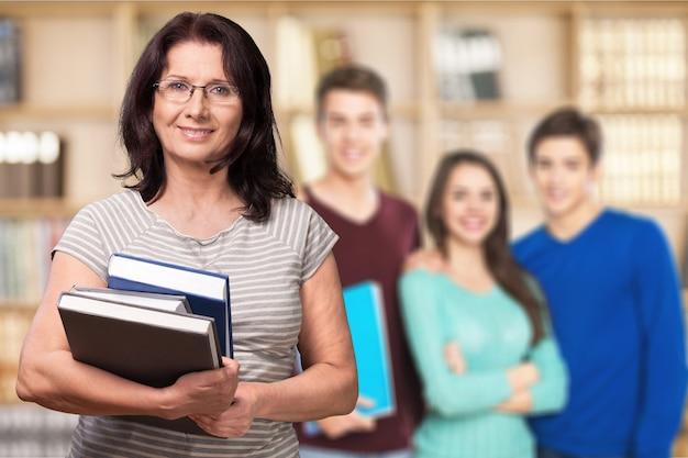Dojrzała uśmiechnięta kobieta z książkami, nauczycielem i uczniami