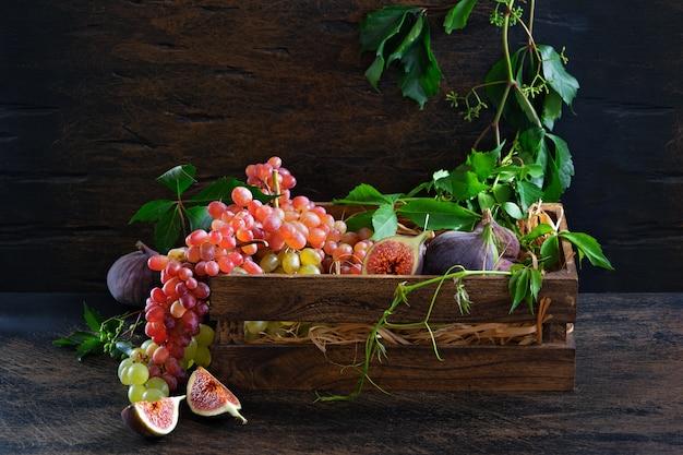 Dojrzała wiązka czerwonych i zielonych winogron oraz białego wina w karafce na starych drewnianych deskach