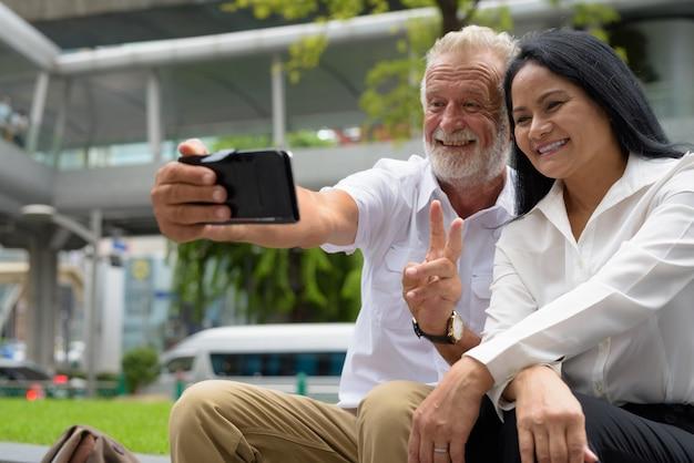 Dojrzała wieloetniczna para szczęśliwa i zakochana podczas zwiedzania bangkoku