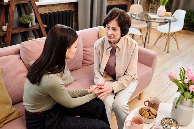 Dojrzała wspierająca kobieta doradczyni trzymająca się za ręce młodej zdenerwowanej kobiety siedzącej na kanapie obok niej i pocieszająca ją w kłopotach