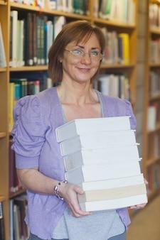 Dojrzała żeńska bibliotekarka pozuje trzymający stos książki