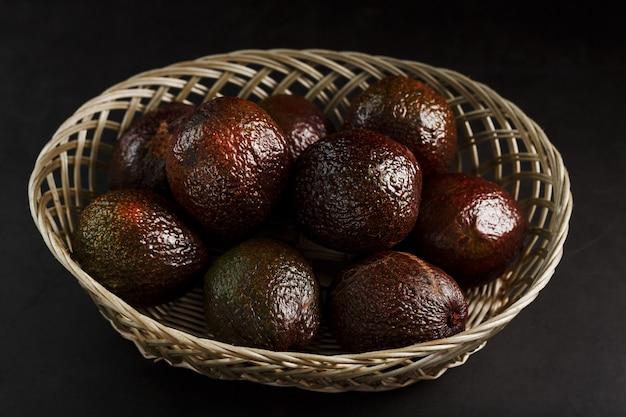 Dojrzałe awokado w koszu na czarnym stole, z pokrojonym owocem i kamieniem. wolna przestrzeń, widok z góry