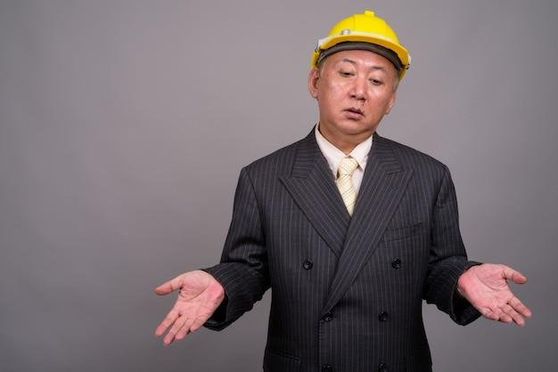 Dojrzałe azjatyckie biznesmen budowy przeciw szarej ścianie