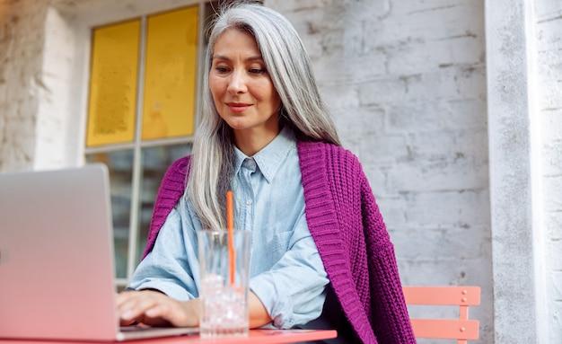 Dojrzałe azjatyckie bizneswoman typy na klawiaturze laptopa siedząc przy stoliku kawiarnianym