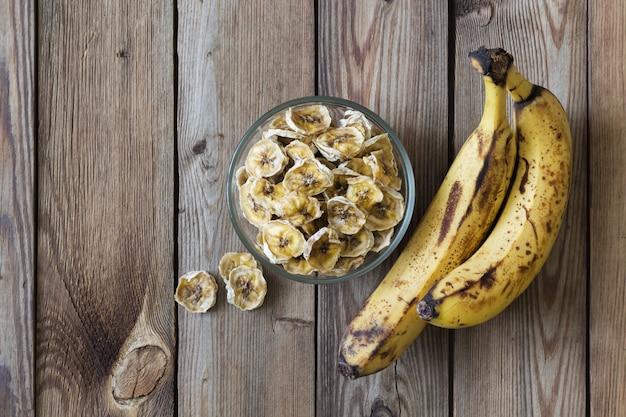 Dojrzałe banany i chipsy bananowe w misce na naturalnym drewnianym stole. skopiuj miejsce