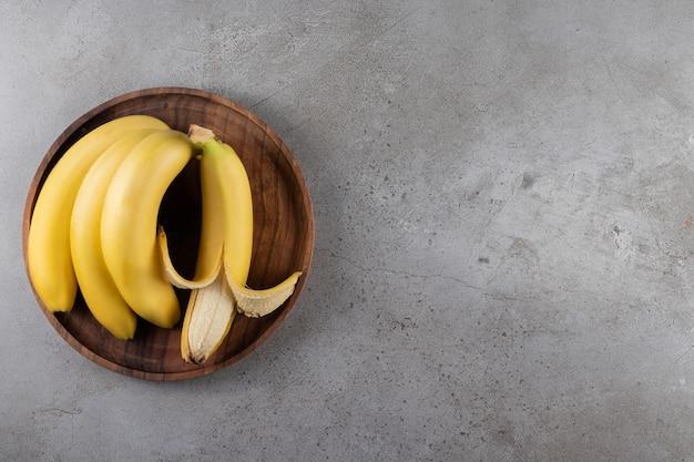 Dojrzałe banany na drewnianym talerzu, na marmurowej powierzchni
