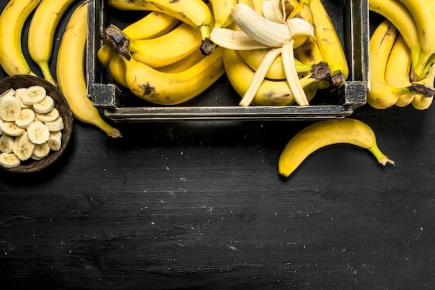 Dojrzałe banany w starym pudełku. na czarnej tablicy.