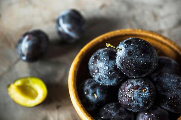 Dojrzałe błękitne śliwki w glinianym pucharze na popielatym stole. koncepcja sezonowych owoców letnich