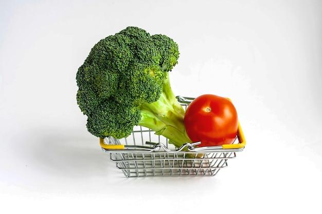 Dojrzałe brokuły i pomidory w koszu żywności na białym tle