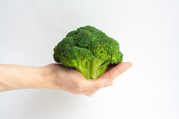 Dojrzałe brokuły w kobiecej dłoni na białym tle