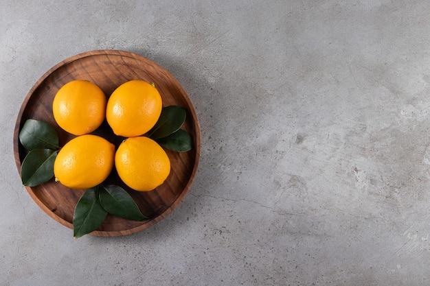 Dojrzałe cytryny na drewnianym talerzu, na marmurowej powierzchni