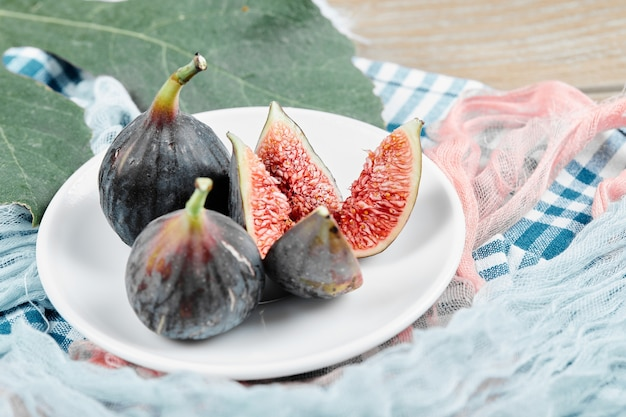 Dojrzałe czarne figi na białym talerzu z listkiem i obrusami.