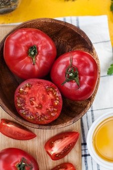 Dojrzałe czerwone i różowe pomidory w całości i pokrojone na drewnianej desce zdjęcie żywności dla ekomarketu