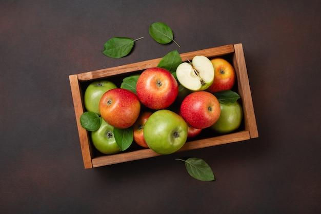 Dojrzałe czerwone i zielone jabłka w drewnianym pudełku na zardzewiałym tle. widok z góry z miejscem na tekst.