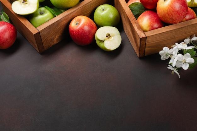 Dojrzałe czerwone i zielone jabłka w drewnianym pudełku z gałęzi białych kwiatów na zardzewiałym tle. widok z góry z miejscem na tekst.