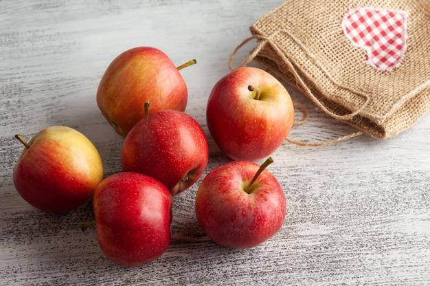 Dojrzałe czerwone jabłka i torba z sercem na rustykalnym stole. jesienne surowe jedzenie