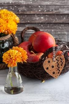 Dojrzałe czerwone jabłka i żółta chryzantema na rustykalnym stole. jesienny wystrój z sercem