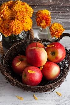 Dojrzałe czerwone jabłka i żółta chryzantema na rustykalnym stole. jesienny wystrój