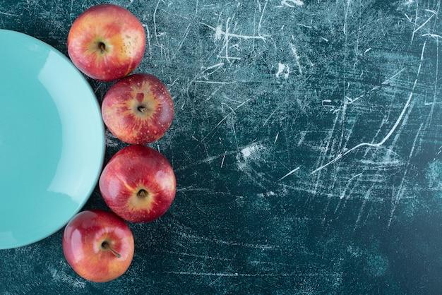 Dojrzałe czerwone jabłka na niebieskim talerzu.