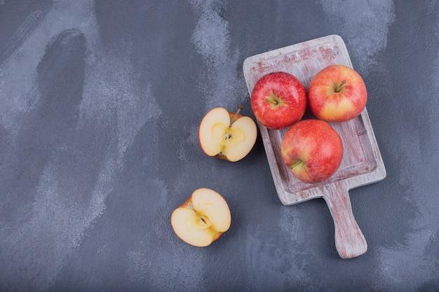 Dojrzałe czerwone jabłka na niebieskim tle.