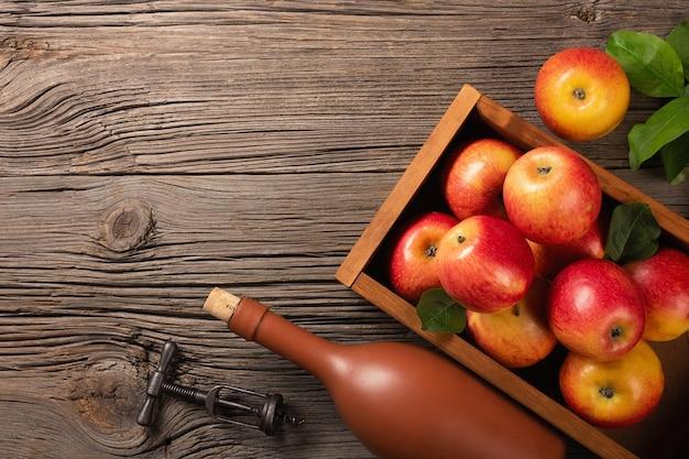 Dojrzałe czerwone jabłka w drewnianym pudełku z gałęzi białych kwiatów, szkła i butelki cydru na drewnianym stole. widok z góry z miejscem na tekst.