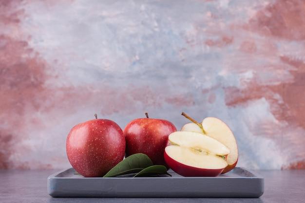 Dojrzałe czerwone jabłka z liśćmi ułożonymi na kamieniu.