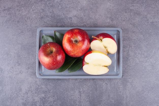 Dojrzałe czerwone jabłka z liśćmi ułożonymi na kamiennej powierzchni.