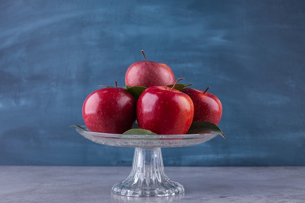 Dojrzałe czerwone jabłka z liśćmi ułożonymi na szklanym talerzu.