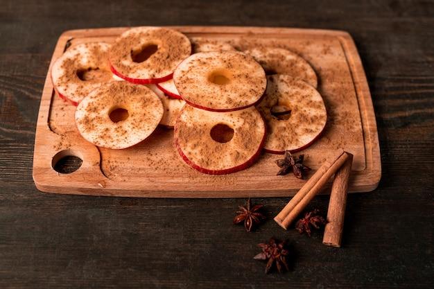 Dojrzałe czerwone jabłko, dwie laski cynamonu, anyż i drewniana deska do krojenia z kawałkami świeżych owoców posypana mielonymi przyprawami