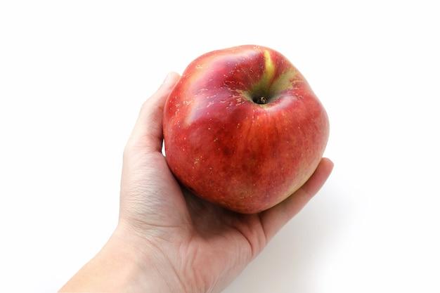 Dojrzałe czerwone jabłko w ręku na białym tle.