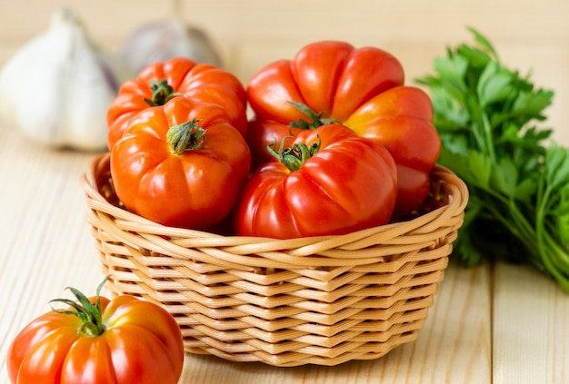 Dojrzałe czerwone pomidory w koszu na jasnym tle drewniane.