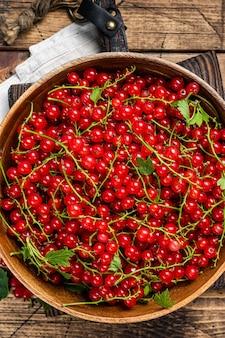 Dojrzałe czerwone porzeczki jagody w drewnianym talerzu. drewniane tła. widok z góry.