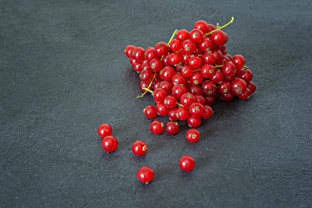 Dojrzałe czerwone porzeczki na ciemnym tle. świeże letnie jagody, zdrowe witaminy.